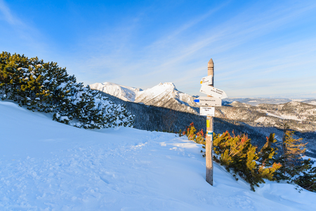 giewont: Sign on hiking trail and view of Giewont mountain in early morning light after sunrise in Tatra Mountains, Poland Stock Photo