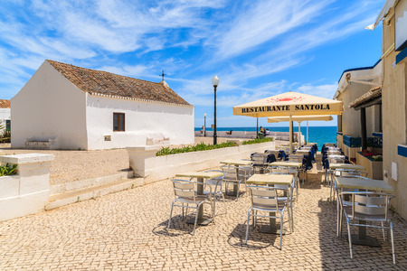 ARMACAO DE PERA TOWN, PORTUGAL - MAY 17, 2015: restaurant tables and white church on coastal promenade in Armacao de Pera seaside town. Algarve region is popular holiday tourist destination in summer.