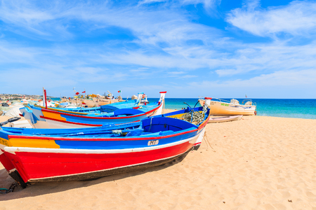 ARMACAO DE PERA BEACH, PORTUGAL - MAY 17, 2015: colorful typical fishing boats on beach in Armacao de Pera coastal village. Algarve region is popular holiday tourist destination on coast of Portugal