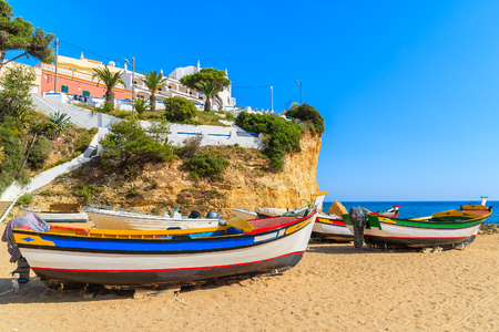 Typical fishing boats on beach in Carvoeiro coastal village, Portugal