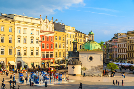 mickiewicz: KRAKOW, POLAND - APR 29, 2015: colorful houses and small church on main market square of Krakow city. More than 10 Million touri