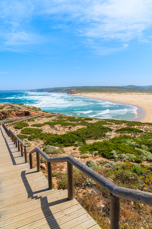 windsurf: Wooden walkway to Praia do Bordeira beach and beautiful blue sea view, Algarve region, Portugal