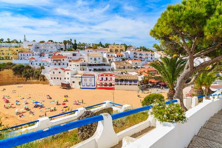 Passeggi lungo la via nel paesino di pescatori di Carvoeiro con la vista delle case variopinte sulla spiaggia, Algarve, Portogallo