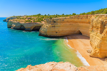 View of beach with golden color cliff rocks near Carvoeiro town, Algarve region, Portugal 免版税图像