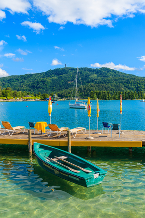 WORTHERSEE LAKE, AUSTRIA - JUN 20, 2015: tourist boats and sunchairs with umbrellas on wooden pier of beautiful alpine lake Wort Editorial