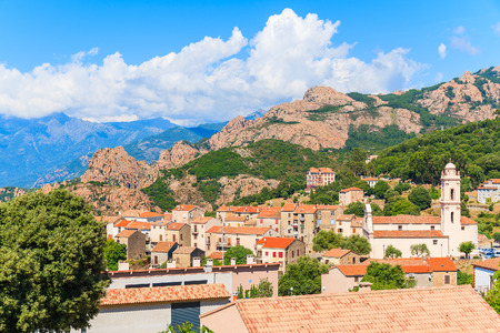 View of Piana village with church tower in mountain landscape of western Corsica, France 免版税图像
