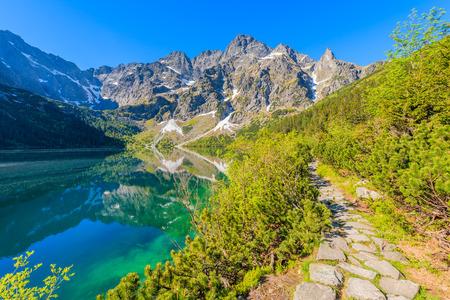 morskie: Path along beautiful green water Morskie Oko lake in summer, Tatra Mountains, Poland Stock Photo