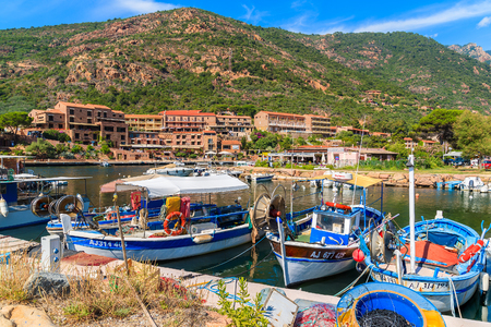 ideally: PORTO HARBOUR, CORSICA ISLAND - JUN 27, 2015: colourful fishing boats mooring in Porto village to the west of Corsica, ideally p