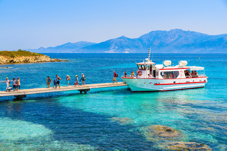 CORSICA ISLAND, FRANCE - JUL 3, 2015: tourists getting off boat and walking on pier to Lotu beach, Corsica island, France. This