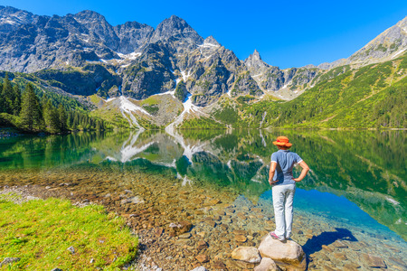 Woman tourist standing on stone looking at beautiful green water Morskie Oko lake, Tatra Mountains, Poland