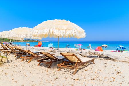Sunbeds with umbrellas on Bodri beach, Corsica island, France