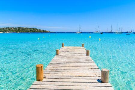 Pilastro di legno e acqua di mare cristallina del turchese sulla spiaggia di Santa Giulia, isola di Corsica, Francia