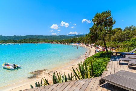 Lettini sulla piattaforma di legno con la vista della spiaggia di Santa Giulia, isola di Corsica, Francia