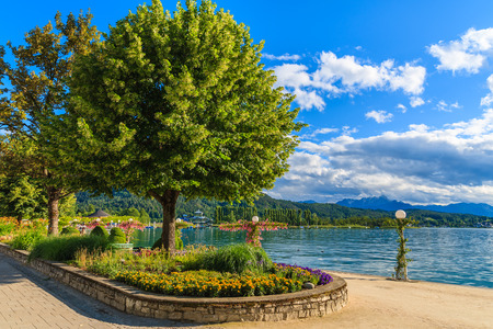 Promenade with flowers along Worthersee lake on beautiful summer day, Austria