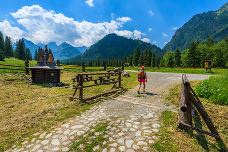 Young woman backpacker walking on hiking trail in High Tatra Mountains in summer, Slovakia