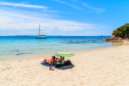 Unidentified couple of people sunbathing on beautiful sandy Grande Sperone beach, Corsica island, France Editorial