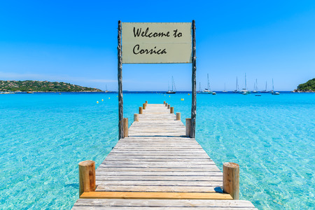 Sign on wooden jetty on Santa Giulia beach with words Welcome to Corsica greeting painted on board, Corsica island, France