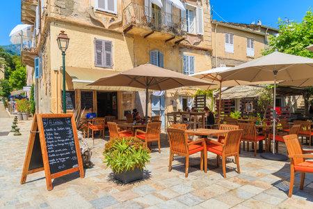 sunshade: ERBALUNGA, CORSICA ISLAND - JUL 4, 2015: restaurant in old part of Erbalunga village. This village is located on Cape Corse, fam Editorial