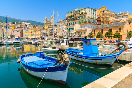 Traditional fishing boats in Bastia port on sunny summer day, Corsica island, France 免版税图像