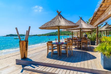Restaurant tables on beautiful beach in Saint Cyprien coastal town, Corsica island, France Reklamní fotografie - 73937867