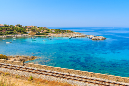 Railway track along beautiful bay in Algajola village on coast of Corsica island, France