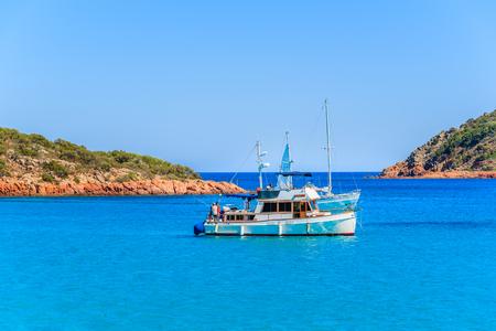 CORSICA ISLAND, FRANCE - JUN 23, 2015: fishing boat on azure sea water in beautiful Rondinara bay, Corsica island, France