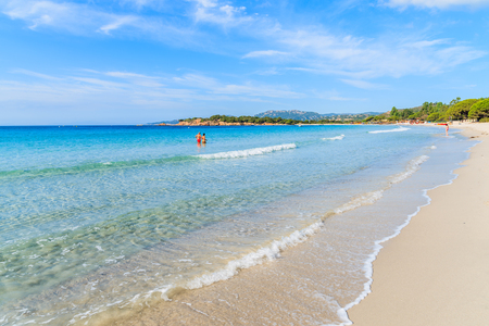 Unidentified couple of people walking in water on beautiful Palombaggia beach, Corsica island, France