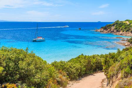 Path to Grande Sperone beach with catamaran boat on sea in distance, Corsica island, France