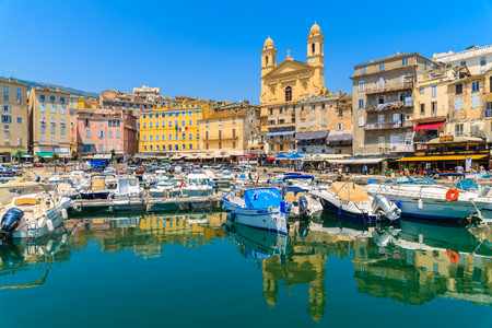 BASTIA PORT, CORSICA ISLAND - JUL 4, 2015: reflection of buildings and cathedral Joannis Babtistes in Bastia port on sunny summe 新闻类图片