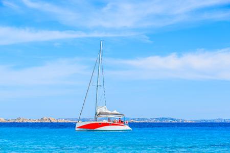 A catamaran sailing on blue sea along a coast of Corsica island, France