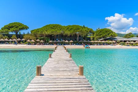 Molo di legno e acqua di mare del turchese sulla bella spiaggia di Santa Giulia, isola di Corsica, Francia Archivio Fotografico