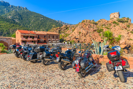 ideally: PORTO, CORSICA ISLAND - JUN 27, 2015: row of motorcycles parked in Porto. It is a small village to the west of Corsica, ideally Editorial