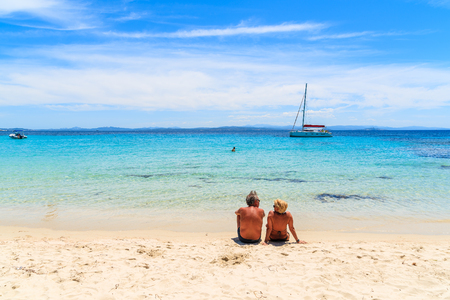 Unidentified couple of people on beautiful sandy Grande Sperone beach, Corsica island, France