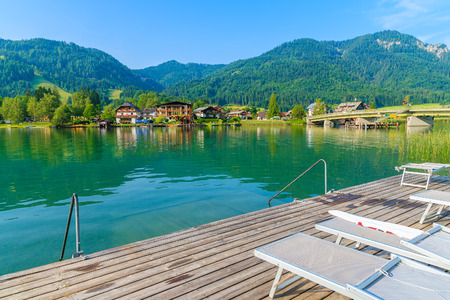 Sunbeds on wooden pier on shore of Weissensee lake in summer landscape of Carinthia land, Austria