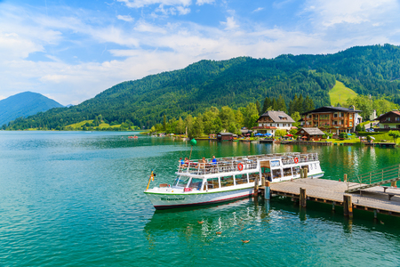 WEISSENSEE LAKE, AUSTRIA: tourist boat Weissensee mooring to pier on shore of Weissensee lake in summer landscape Editorial