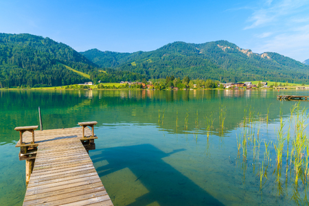 Wooden pier and view of beautiful Weissensee lake in summer landscape of Alps Mountains, Austria 스톡 콘텐츠