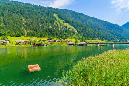 Wooden platform for swimming on green water Weissensee lake in summer landscape of Alps mountains, Austria