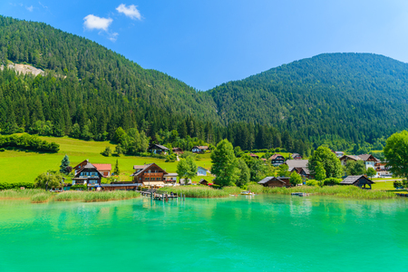 Houses on shore of beautiful Weissensee alpine lake in summer landscape of Alps Mountains, Austria