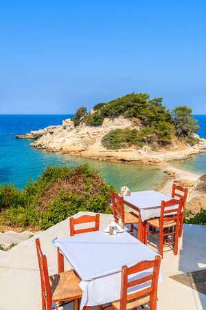 Tables with chairs in typical Greek tavern in Kokkari bay, Samos island, Greece