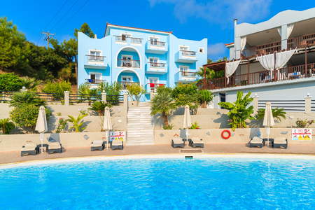 SAMOS ISLAND, GREECE - SEP 20, 2015: view of swimming pool and colorful hotel buildings on sunny summer day, Samos island, Greece Editorial