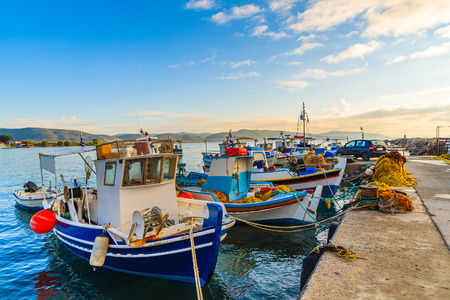 Colourful Greek fishing boats mooring in port at sunrise time on Samos island, Greece