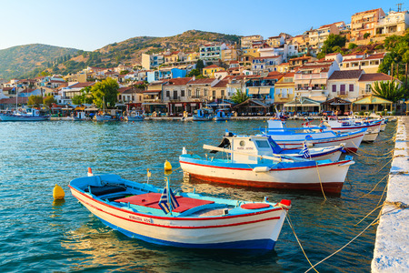 SAMOS ISLAND, GREECE - SEP 18, 2015: colorful Greek fishing boats in Pythagorion port at sunset time. Editorial