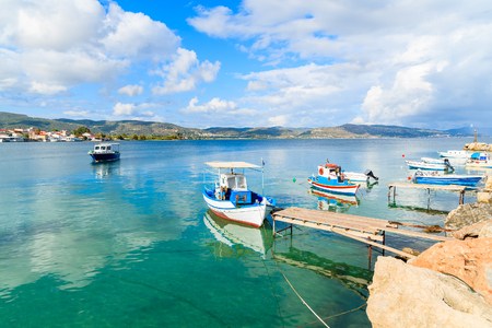 Greek fishing boats on turquoise sea water mooring in port, Samos island, Greece Stock Photo