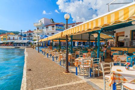 KOKKARI, SAMOS ISLAND - SEP 25, 2015: Tables with chairs in traditional Greek tavern in Kokkari town on coast of Samos island, Greece