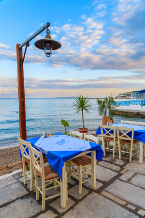 Tables with chairs in Greek restaurant on sea coast at sunset time, Samos island, Greece 版權商用圖片