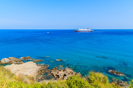 Ferry ship on blue sea sailing along coast of Samos island, Greece.