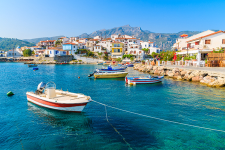 Fishing boats in Kokkari bay with colourful houses in background, Samos island, Greece Stock Photo
