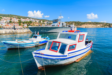 Typical colourful fishing boats with warship in background in Pythagorion port, Samos island, Greece