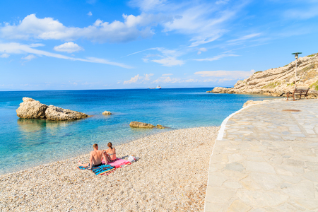 Couple of unidentified people relaxing on beautiful Kokkari beach, Samos island, Greece