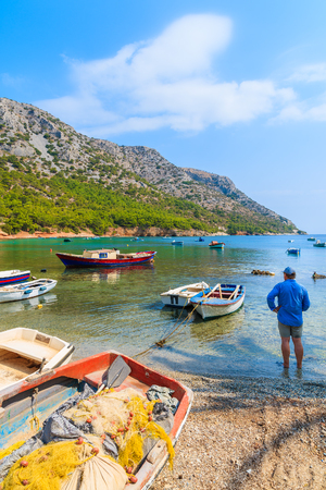 Fisherman standing among fishing boats on secluded beach, Samos island, Greece